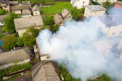 Aerial view of a house on fire with orange flames and white thick smoke.
