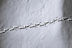 Aerial view of a human footprints in the snow of a hiker on snowshoes. Top view human footprints in deep snow.