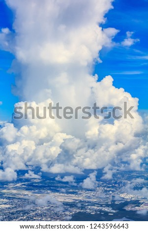 Aerial view of a large and fluffy cumulous cloud above the Miami International Airport in Florida