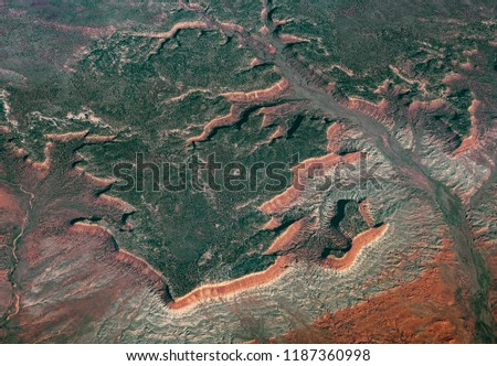Aerial view of a large plateau covered by a forest and erosion formations created by a branched river #1187360998