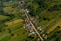 Aerial view of a linear village. Households are bordered by agriculture fields
