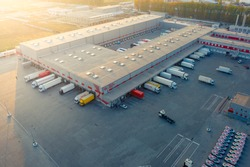 Aerial view of a logistics park with warehouse, loading hub and many semi trucks with cargo trailers standing at the ramps for load/unload goods at sunset.