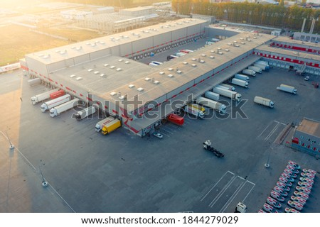 Aerial view of a logistics park with warehouse, loading hub and many semi trucks with cargo trailers standing at the ramps for load/unload goods at sunset.  Foto stock ©