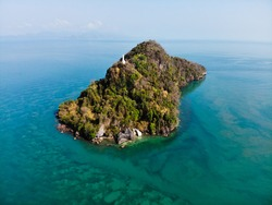 Aerial view of a lonely rocky island covered with greenery in the middle of the sea. There's a building on top of the island. Malaysia
