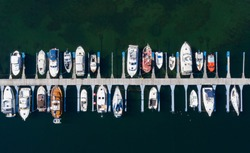 Aerial view of a lot of white boats and yachts moored in marina. Photo made by drone from above. Summer, Norway, Sognefjord, village Vik.