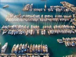 Aerial view of a lot of white boats and yachts moored in marina. Turkey Riviera during sunset, yachts in marina Aegean sea with sen rays. Luxury yacht moored in the bay