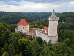 Aerial view of a medieval castle Kokorin. Fortified stone palace with a tower and a wall, red roofs, standing on a hill covered by trees.  Castles in the Central Bohemian Region, Czech republic.