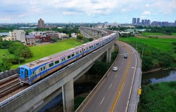 Aerial view of a metro train of Taoyuan Airport MRT System travels on the elevated rails, which is parallel to a highway, on a beautiful sunny day, in Zhongli District, Taoyuan City, Taiwan