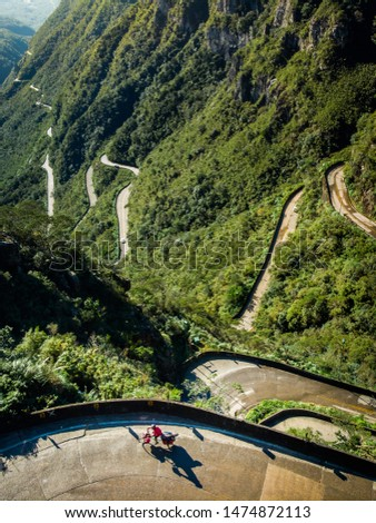 Aerial view of a mountain forest curve road with a cyclist climbing. Scenic landscape of an asphalt snake. Concept of nomadic road trip, challenge, success, perseverance. Serra Rio do Rastro, Brazil.