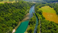 Aerial view of a mountain freshwater river surrounded by green trees at a hydroelectric power station. Green energy on the planet. Ecology. The rocky bottom of the river. drone video. Trezzo sull'Adda