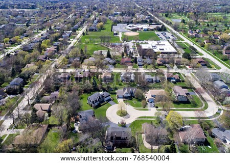 Aerial view of a neighborhood in the suburban Chicago area with homes, cul-de-sac; parks, baseball diamond, tennis courts and swimming pools.