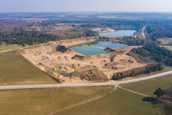 Aerial view of a opencast sand, gravel mine quarry full with green water