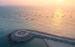 Aerial view of a p-shaped jetty reinforced with tetrapods (wave breaker blocks) & golden sunlight reflected in the seawater dotted with oyster farming rafts off Yuguang Island, Anping, Tainan, Taiwan
