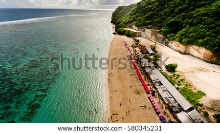 Aerial view of a Pandawa beach with many umbrellas and people relaxing. Bali, Indonesia.