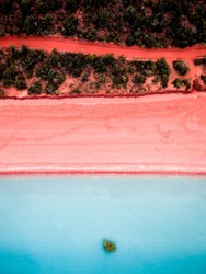 Aerial view of a pink sand beach and red dirt road next to Roebuck Bay in Broome, Western Australia.