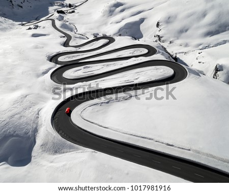 Aerial view of a red car traversing Julier Pass in the Swiss Alps