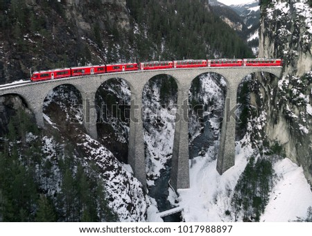 Aerial View of a red train crossing the Landwasser Viaduct in the Swiss Alps