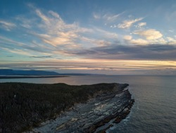 Aerial view of a rocky shore on the Atlantic Ocean Coast during a vibrant sunny sunset. Taken in Cow Head, Newfoundland, Canada.