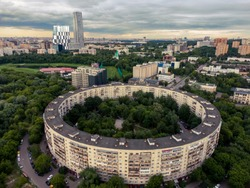 Aerial view of a round house in Moscow, skyscrapers in the background, summer nature in the frame. Aerial photography