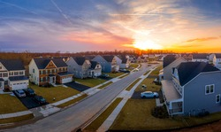 Aerial view of a row of multi story single family homes real estate properties in a new residential suburban neighborhood street in Maryland USA with dramatic colorful sunset sky