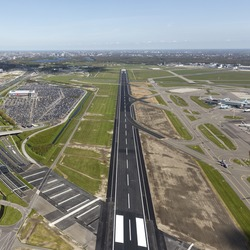 Aerial view of a runway at Schiphol Amsterdam Airport with the city on the clear blue horizon. The runway looks like a highway.