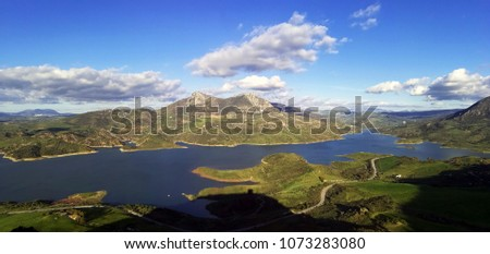 Aerial view of a scenic meadows landscape in a lake against mountains.  #1073283080