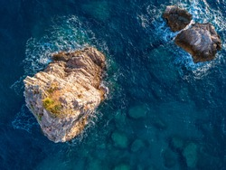 Aerial view of a seabed with rocks emerging from the sea, seabed seen from above, transparent water