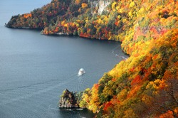 Aerial view of a sightseeing boat cruising on magnificent Lake Towada in autumn season, in Towada Hachimantai National Park, Aomori, Japan ~ Breathtaking scenery of grand nature in Northeastern Japan