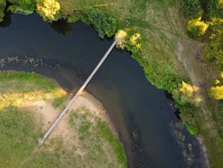 Aerial view of a simple suspension bridge over a small river. Summer landscape, river with footbridge, top view. Hanging bridge across river