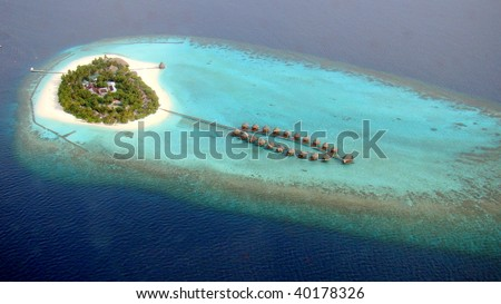 Aerial view of a small island and water villas, Maldives