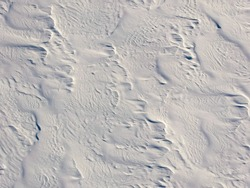 Aerial view of a snowy field crossed by snow waves
