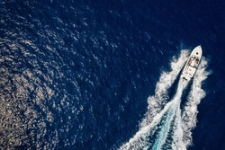 Aerial view of a speedboat traveling over blue sea leaving a trail of white waves and bubbles behind with copyspace