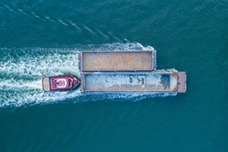 Aerial view of a tug boat pushing two coal barges on the Hudson River in New York City