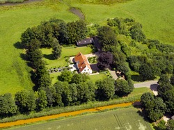 Aerial view of a white fram house surrounded by trees and agricultural flat land in the Netherlands. Remote farm, living in the Dutch countryside. Birds eye view of Large white house  and red rooftop.
