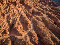 aerial view of a windy 4WD road through red sandstone canyon with coarse vegetation near Moab, Utah