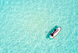 Aerial view of a woman on a surfboard in the turquoise waters of the Maldives