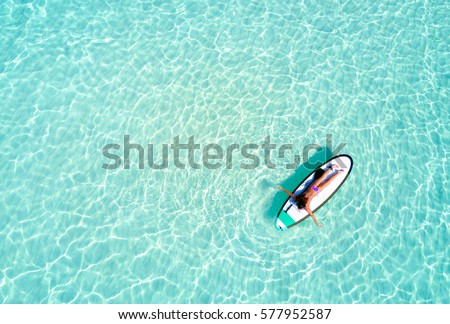 Aerial view of a woman on a surfboard in the turquoise waters of the Maldives #577952587