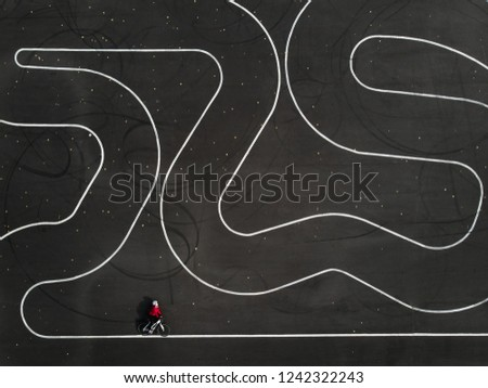 Aerial view of a woman riding a bike on a parking lot. Zigzag track lines on the asphalt. #1242322243
