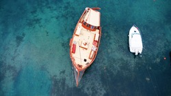 Aerial view of a wooden boat in the sea in Chalkidiki, Greece.