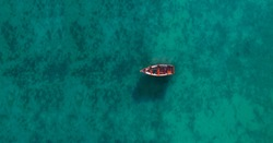 Aerial view of a wooden boat in the water, ship and boat in a beautiful turquoise ocean near an island, top view, aerial photo