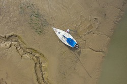 Aerial view of a yacht aground on a muddy shore in Southampton in the United Kingdom. Image with space for text.