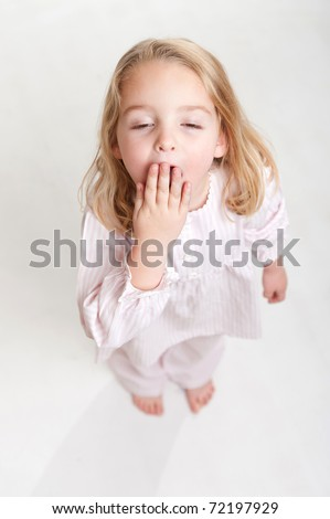 Aerial view of a yawning blonde little girl in her pajamas