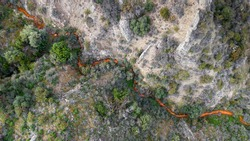 Aerial view of acid drainage from an abandoned copper mine in Kalavasos area, Cyprus. Odd red color of the stream derives from high levels of sulfuric acid and heavy metals