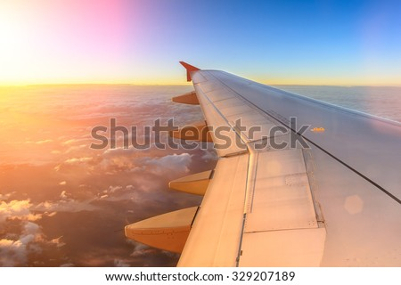 Aerial view of airplane flying above shade clouds and sky from an airplane fly during the sunset. View from the plane window of emotional moment during international travel around the world.  #329207189