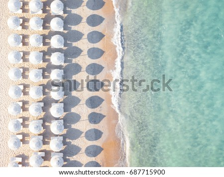Aerial view of amazing beach with white umbrellas and turquoise sea at sunset. Mediterranean sea, Sardinia, Italy.