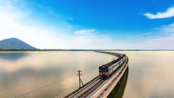 Aerial view of amazing Thailand travel train look like floating above the lake of Pa Sak Jolasid dam with blue sky. Unseen Train is running on the railway bridge over the reservoir at Lopburi Thailand