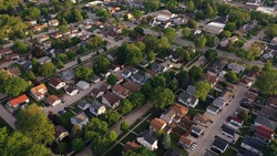 Aerial view of american suburb at summertime.  Establishing shot of american neighborhood. Real estate, residential houses. Drone shot, from above