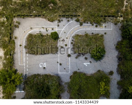 Aerial view of an abandoned parking lot in a rural area already invaded by the vegetation of the area