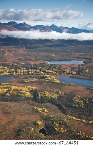 Aerial view of an Alaskan landscape with lakes and mountains in the background.