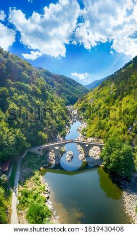 Aerial view of An ancient stone bridge called Devil's bridge near the town of Ardino. Amazing Reflection of Devil's Bridge in Arda river and Rhodopes mountain, Kardzhali Region, Bulgaria